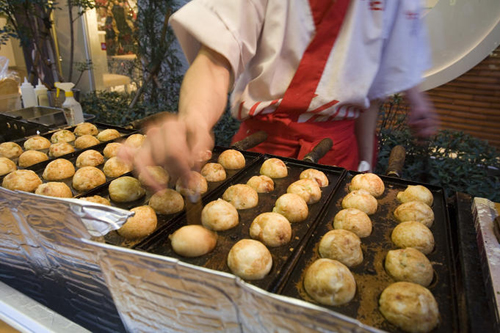 cook prepares takoyaki octopus balls dotonbori Travel To Osaka   Top 10 Best Places