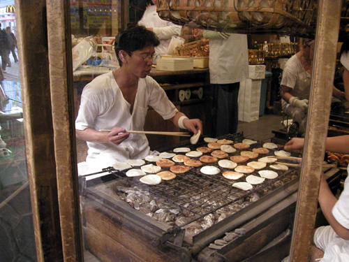 A Japanese guy making senbei at an old store