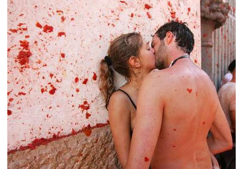 Romantic couple french kissing during the La Tomatina festival. Did you see that. the little love shape at the back of the guy?