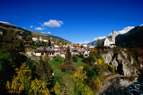 the natural beauty of switzerland old church and village set on cliffs above the inn river with snow covered mountains in the background Travel To Switzerland   Top 10 Best Places