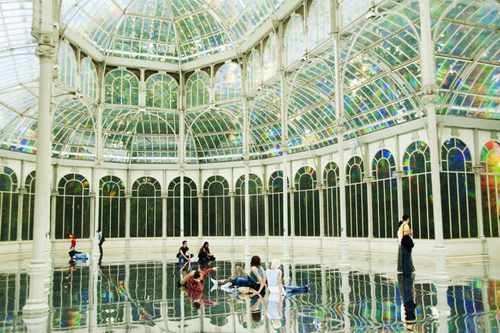 Visitors lying on the floor savoring the mesmerizing interior of Palacio de Cristal in Parque del Buen Retiro.