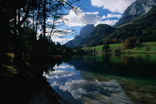 Clouds above, and reflected in, the still waters of Hintersee in the Bavarian Alps weave a memorable landscape.