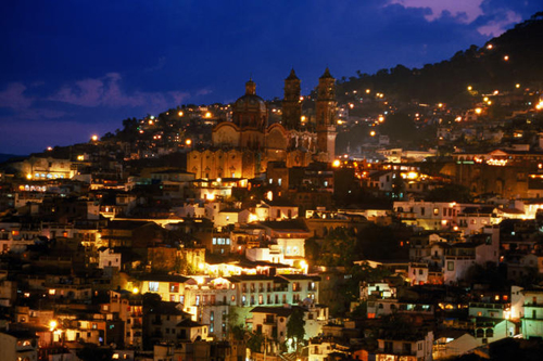 Iglesia Santa Prisca and hillside houses lit up at dusk, Mexico