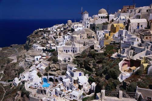 Southern Aegean village of Oia perched on Santorini crater rim.