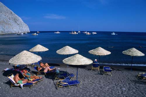 Time out of the rat race on the black sands of Perissa beach on the east coast of Santorini island, Greece