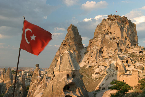 Turkish flag in front of Uchisar Castle, a natural skyscraper of Cappadocia, Turkey