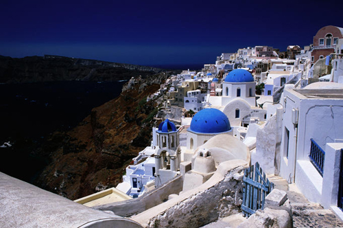 White-washed houses and blue domes on cliff top are just so typically Greek